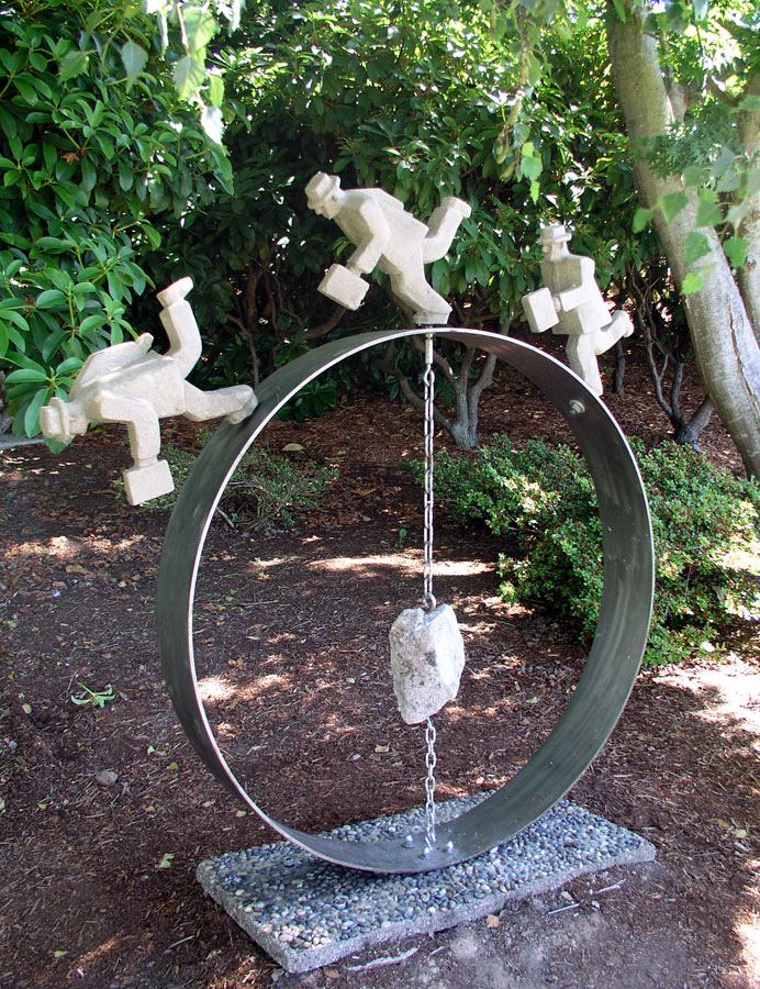 """Off-Centre, November 2002 cast concrete, steel, found rock, chain  55"""" high x 55"""" wide x 8"""" deep shown at Peace Arch Park in 2005"""